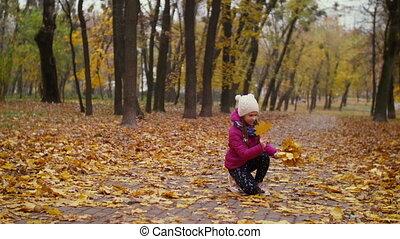 Girl collecting autumn bouquet of fallen foliage - Adorable...