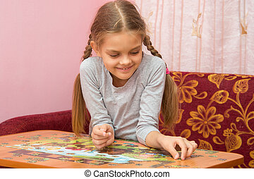 Girl collects a picture from puzzles