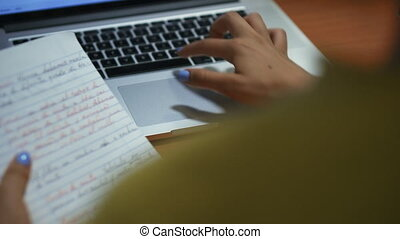 Young woman typing on laptop computer keyboard for homework. Hispanic girl and college education. Female student studying and using pc at home. Over the shoulder shot