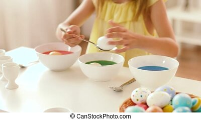girl coloring easter eggs by liquid dye at home - easter,...
