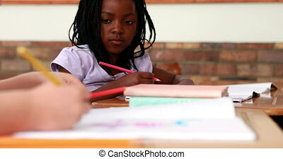 Girl colouring in the classroom - Little girl colouring in...