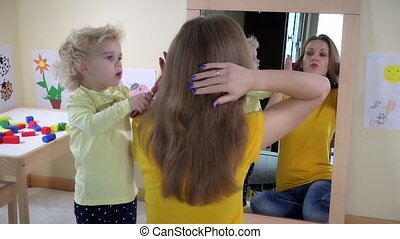 girl combing woman hair in front of mirror