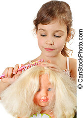 Girl combs doll hair by toy hairbrush isolated on white background