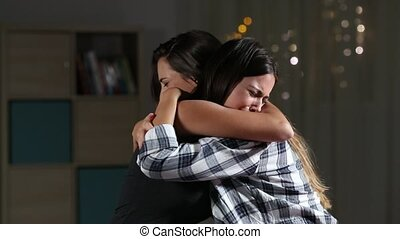 Girl comforting her sad friend at home - Side view of two...