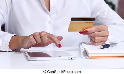 Girl completes an online purchase and enters the data on the card. Close up