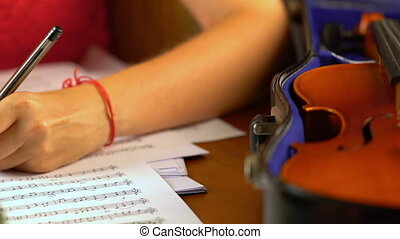 Girl composes music in music sheet book . - Girl composes...