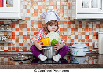 girl cook with fresh vegetables sits on a kitchen table
