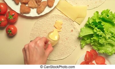 Girl cooking Caesar roll with flatbread, chicken, cheese, salad and tomatoes