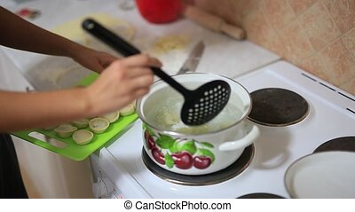 Girl cooking dumplings in pan. A girl prepares food