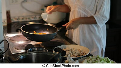 Girl Cooking Vegetables On Frying Pan, Young Woman Stir Preparing Meal In Modern Kitchen