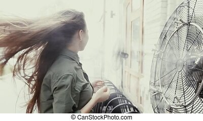 girl cooling herself with fan - Girl is cooled by a fan and...