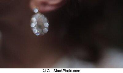 Girl corrects earring with diamond.