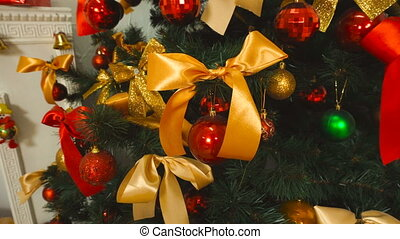 girl corrects Orange bow on the Christmas tree