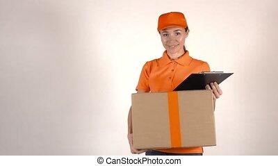 Girl courier in orange uniform delivering a big carton. Light gray backround, 4K studio shot