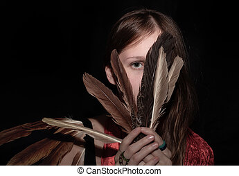 Girl covering the face with feathers