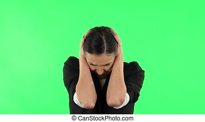 Girl covers her ears, too loud. Girl with dark hair wearing a black business suit at green screen at studio.
