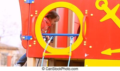 A girl having fun on the playground crawls on his knees at the window