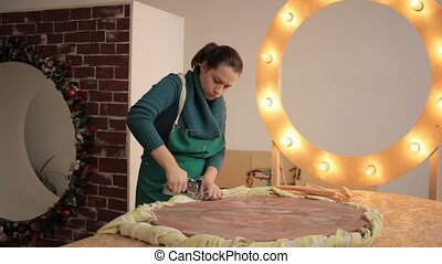 Girl creating decorative item - Woman stapling fabric to...