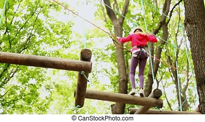 girl crosses on linked logs and suspended on height in wood...