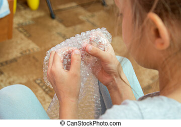 Girl crushes the bubbles on the packaging film