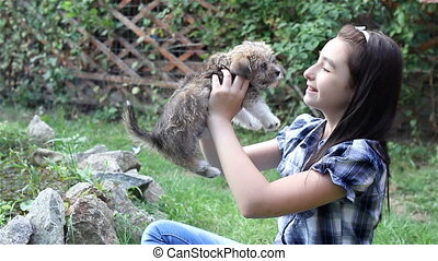 Girl cuddling a puppy outdoors