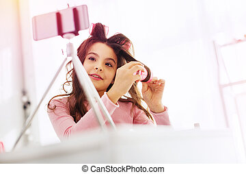 Girl curling her hair in front of phone camera before first day in kindergarten