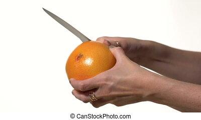Girl cuts a knife peel grapefruit. White background....