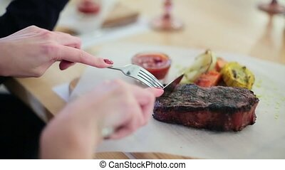 girl cuts a steak in a restaurant