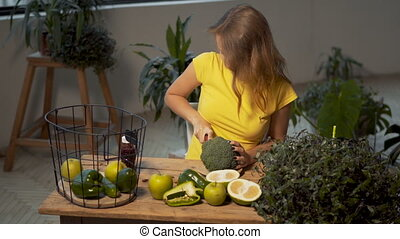Girl Cuts Fresh Broccoli - Smiling girl cutting fresh...
