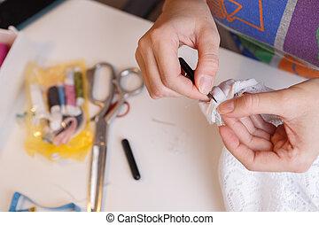 Girl cuts thread in fabric