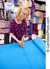 girl cutting fabric in a fabric store