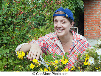 Woman doing garden work cutting the shrubby cinquefoil