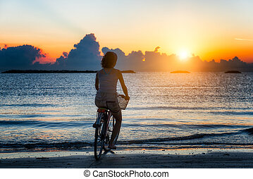Girl cycling in the sea during sunrise