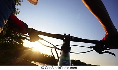 Girl cyclist in gloves walking with her bike. Slow motion shot against sunset