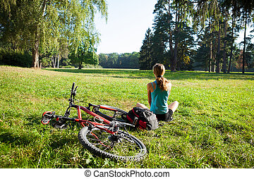 Girl cyclist relax front view panorama of the spring park -...