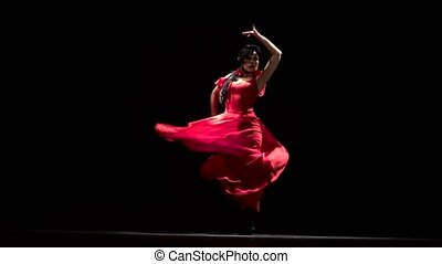 Girl dancer moved in time with the music. Black background -...