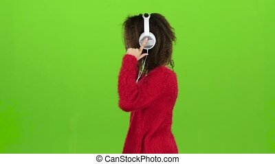 Girl dances and rotates with headphones, green screen. Slow motion