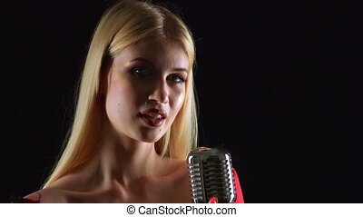 Girl dances and sings in a retro microphone. Black...