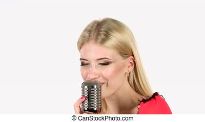 Girl dances and sings in a retro microphone. White...