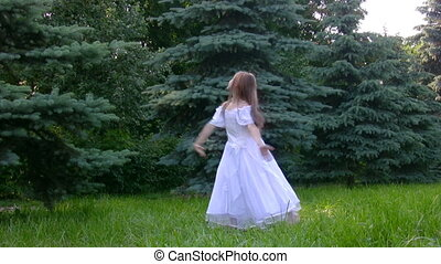 girl dances ballet in park with conifers