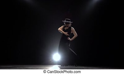 Girl dances flamenco. Black background. - Girl in a hat and...