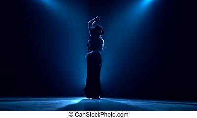 Girl dances flamenco. Blue background. Silhouette - Girl is...