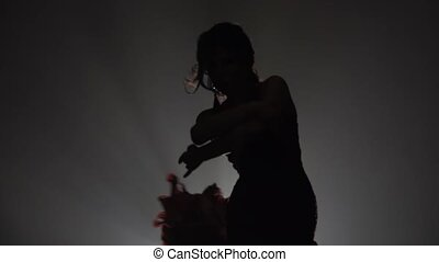 Girl dances flowing movements with her hands standing with her backs. Light from behind. Smoke background. Slow motion. Silhouette