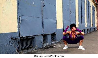 Girl dances in modern style near building