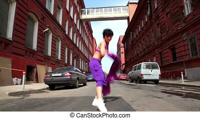 Girl dances in modern style with cloth on street
