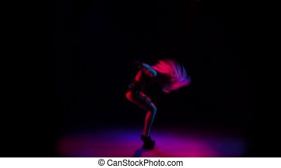 Girl dancing and plays with hair. Slow motion, black studio