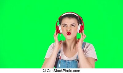 Girl dancing and singing in big red headphones on green screen at studio, slow motion