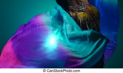 Girl dancing belly dance with a veil in her hands . Smoke...