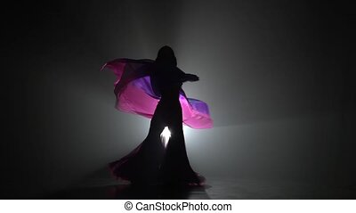 Girl dancing belly dance with shawl. Sihouette . Black smoke...