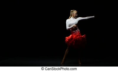Girl dancing cha-cha-cha in a studio on a dark background
